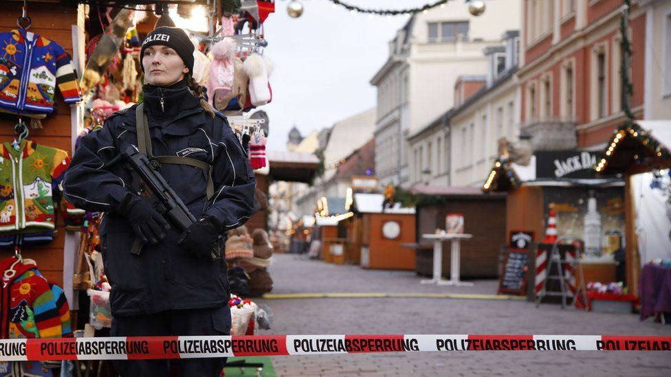 A police officer stands guard behind a police line at the otherwise bustling Potsdam Christmas market, now empty after it was evacuated by police, Potsdam, Germany, 01 December 2017.