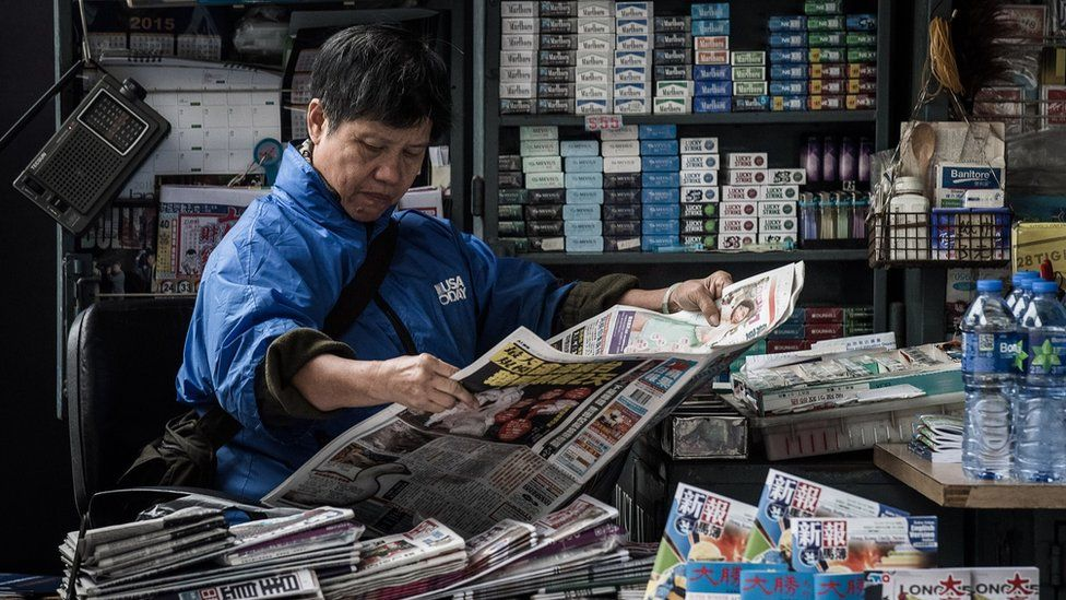 A woman reads a newspaper at a kiosk in Hong Kong on January 12, 2015. Firebomb attacks on the Hong Kong home and office of pro-democracy newspaper tycoon Jimmy have triggered new fears over the safety of outspoken media figures in the city