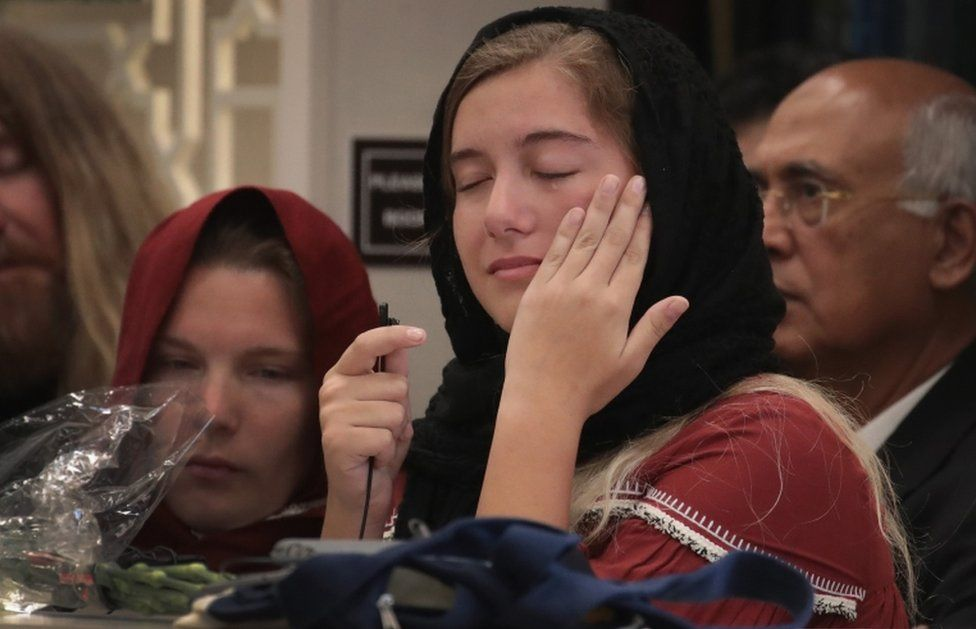 A young girl wipes away a tear at a service honouring shooting victim Sabika Sheikh in Stafford, Texas
