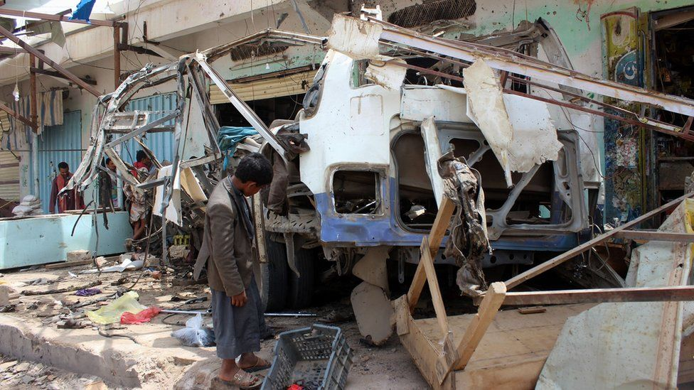 A man inspects a bus destroyed in a Saudi-led coalition air strike in Dahyan, Saada province, Yemen (10 August 2018)