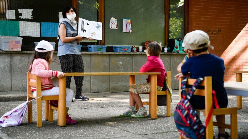 A teacher reads a book to kindergarten children in a school garden. Municipality of Ivrea opens the gardens of two kindergarten schools as part of a pilot test to see how schools can reopen after COVID-19 coronavirus lockdown.