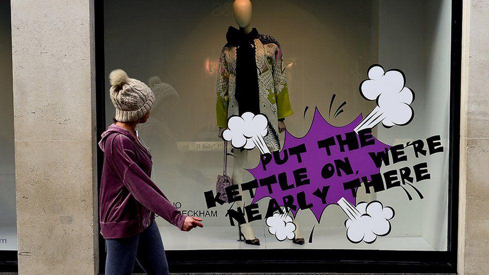 Женщина проходит мимо магазина в Дублине, Ирландия