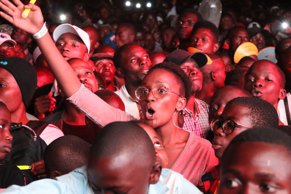 A woman in the audience waving