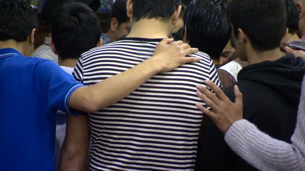 A group of Iranian converts pray with each other
