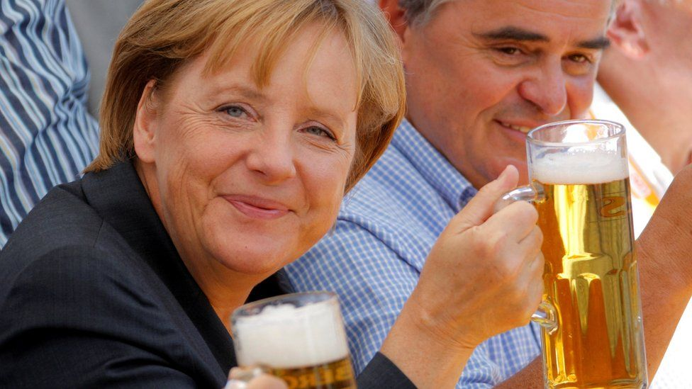 German Chancellor Angela Merkel (L) and Peter Mueller, federal prime minister of the Saar region and top candidate of the of the conservative Christian Democratic Union party (CDU) for the upcoming Saarland state election, hold glasses of beer during an election campaign rally in Bosen near Saarbruecken August 15, 2009