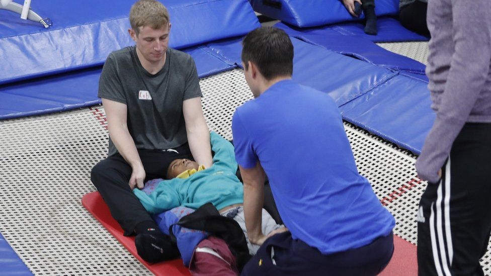 A couple of members of staff supporting a student lying on a trampoline
