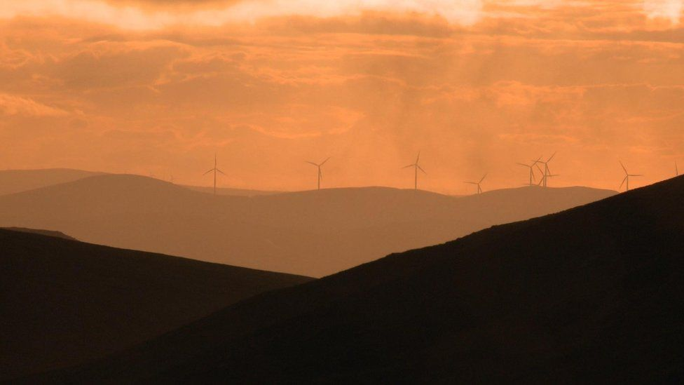 Wind turbines at the summit of Clyde Law, from where water trickles to