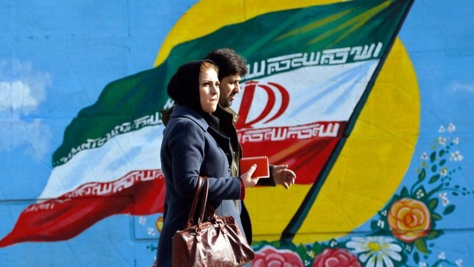 Iranians walk in front of a painting of Iran's national flag in Tehran. File photo