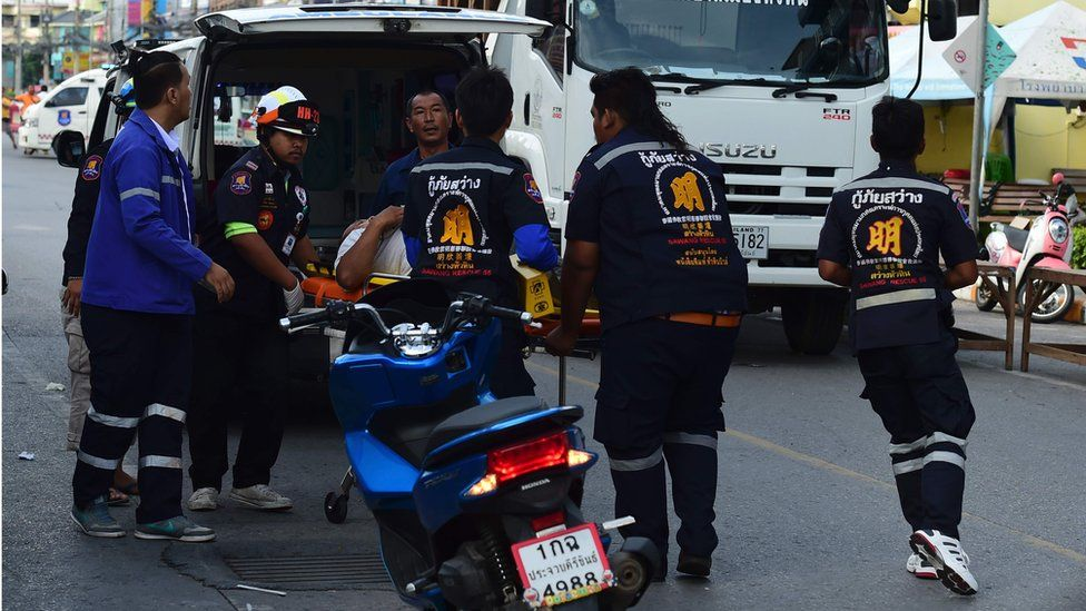 Thai rescue workers carry an injured man on a stretcher to an ambulance, in Hua Hin on 12 August 2016.