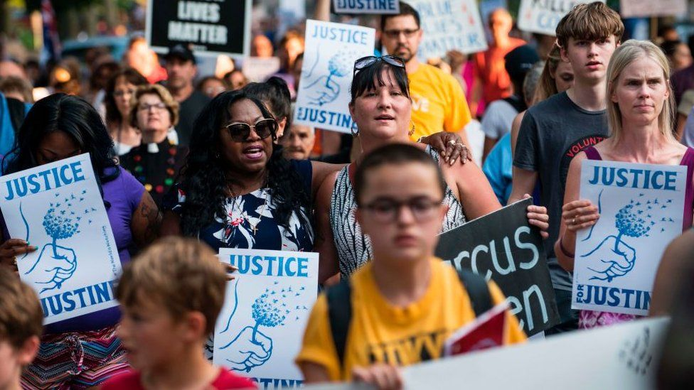 """A march in Minneapolis in 2017 with protestors holding placards saying """"Justice for Justine"""""""