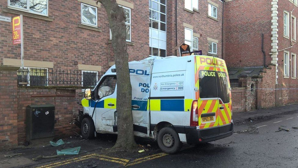 The damaged police van and the smashed wall