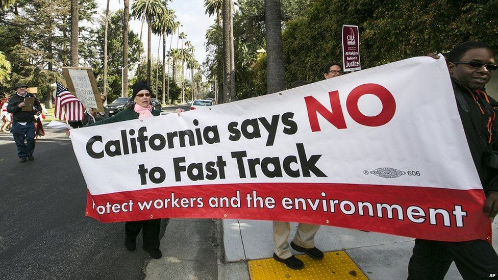 Protestors in hold a sign decrying Fast Track
