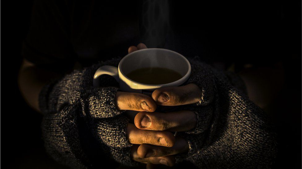Homeless man with cup of tea