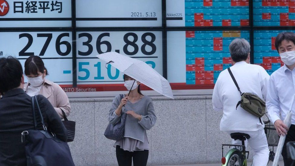 People walk past an electronic quotation board displaying share prices in early morning trading on the Tokyo Stock Exchange in Tokyo on May 13, 2021.