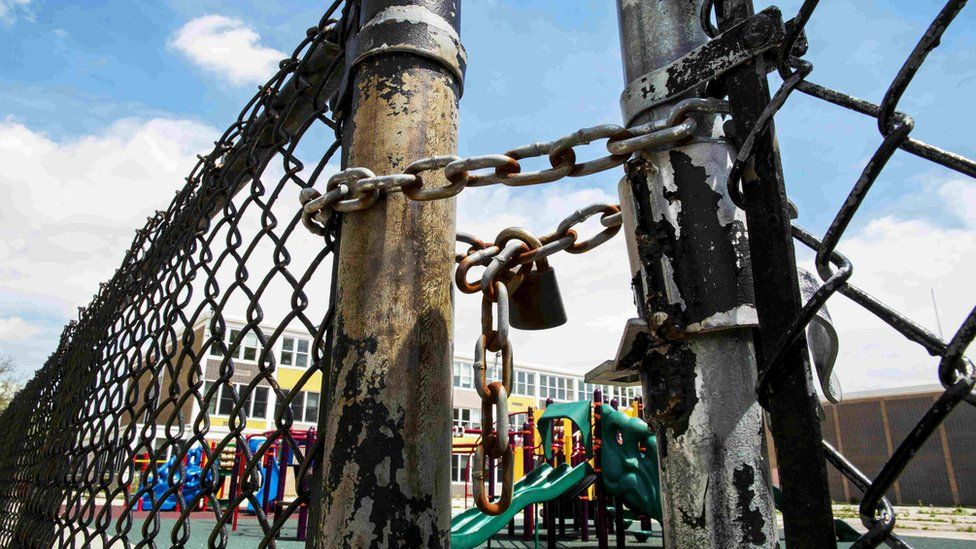 A playground is seen behind a locked gate at Woods Elementary Math and Science Academy in Chicago