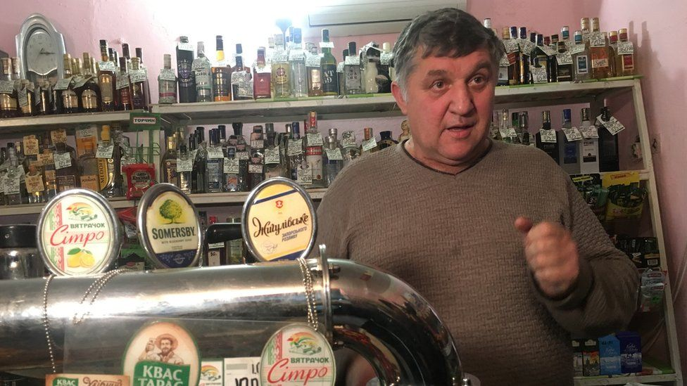 Shop owner Viktor speaking to the BBC in front of a bar