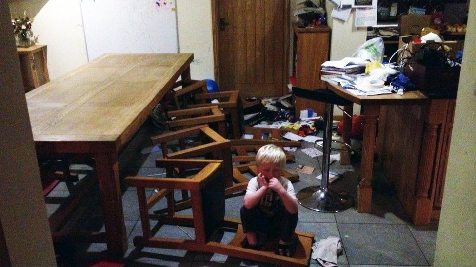 Jamie in the dining room, surrounded by chairs and objects pushed to the floor