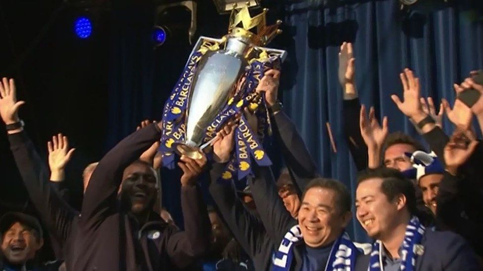 The Thai owners and captain Wes Morgan raise the trophy