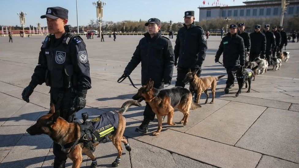 Chinese police officers with sniffer dogs patrol in Tiananmen Square (05 March 2017)