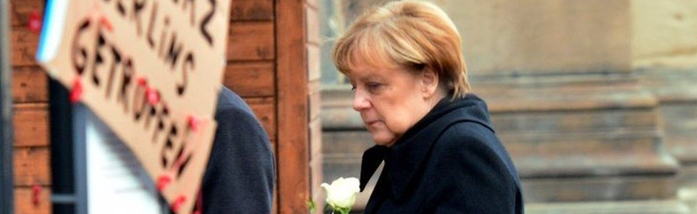 Angela Merkel brings a flower to the site of Monday's attack