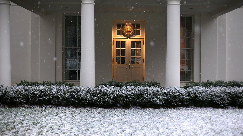 Snow falls in front of the entrance to the West Wing of the White House.