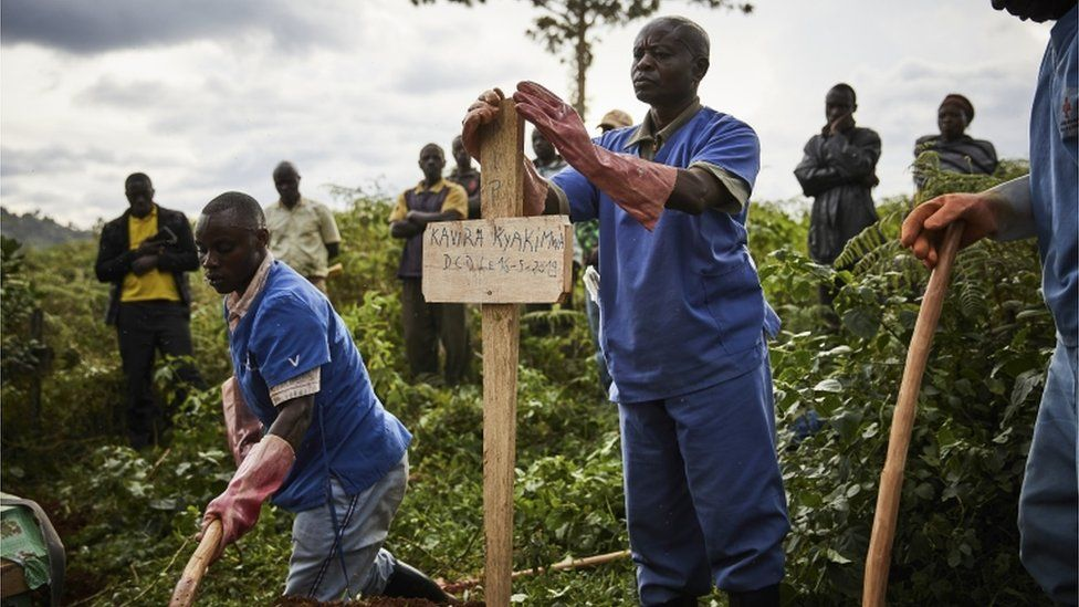 Health workers take part in the funeral of Ebola victims at Kitatumba cemetery in Butembo, North Kivu province
