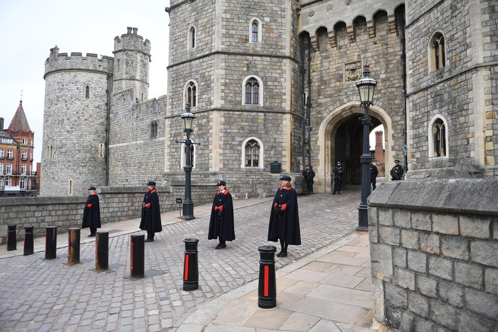Windsor Castle staff stand outside Windsor Castle, a day after the passing of Britain's Prince Philip, in Windsor, Britain, 10 April 2021.