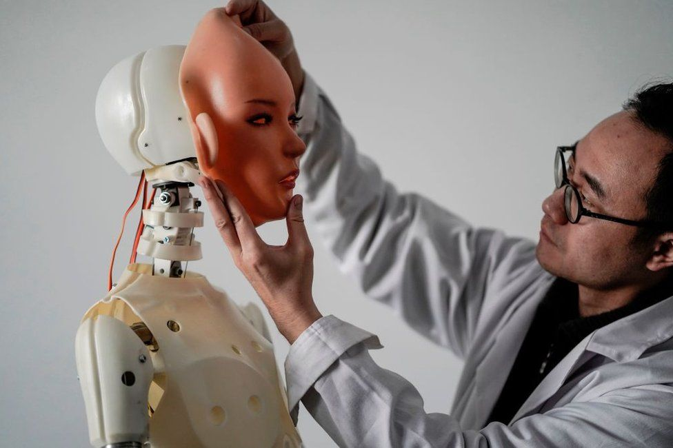An engineer holds a silicon face against the head of a robot at a lab of a Chinese firm Exdoll