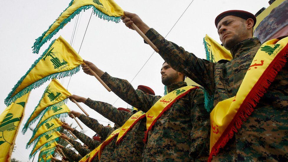 Hezbollah members hold up flags during a funeral for a Hezbollah fighters killed in Syria (2 March 2016)