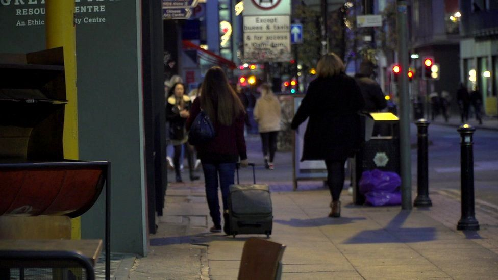 Young woman drags suitcase up street