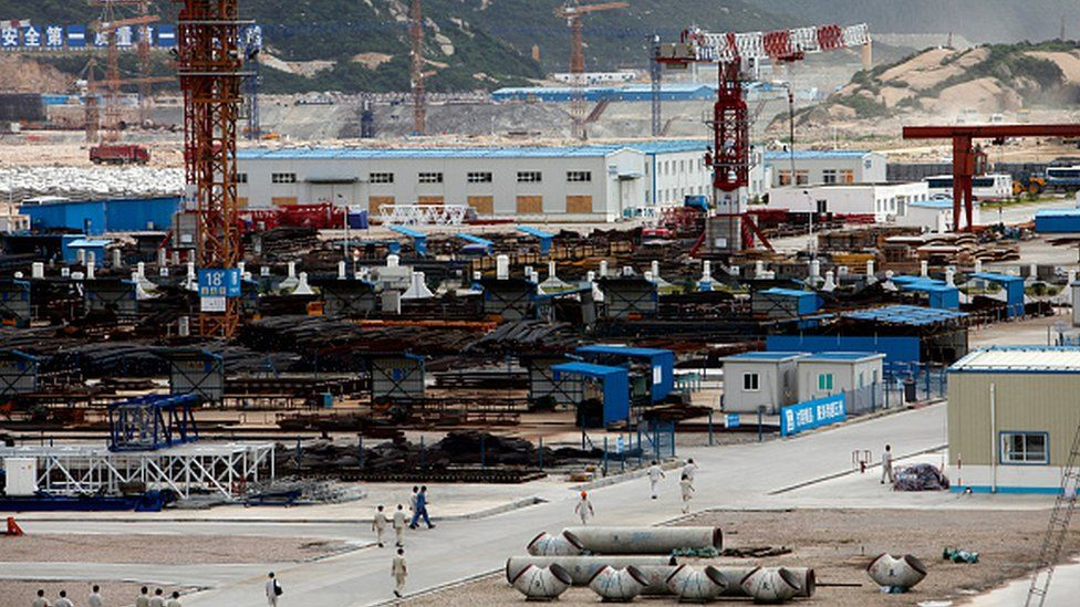 Workers walk through the material supply yard at the Taishan plant