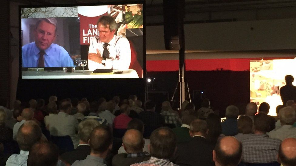 Audience members watch Owen Paterson and Sir Peter Kendall on a large screen during the debate