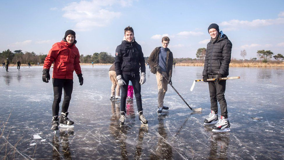 People pose with hockey sticks on a frozen body of water at the Kalmthoutse heide (Kalmthout Heath) nature reserve in Kalmthout on February 28, 2018.