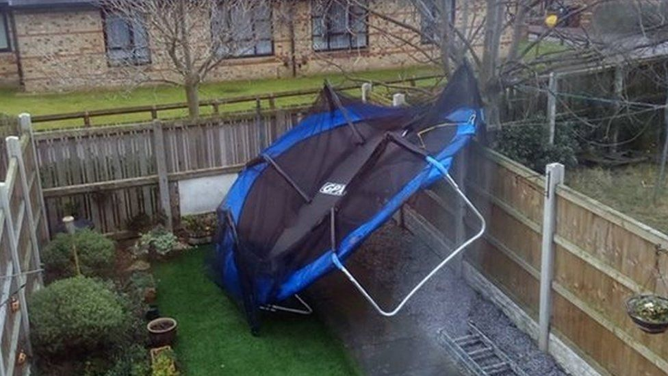 A trampoline which has been blown into a garden