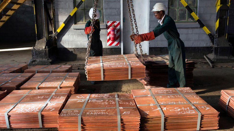 Workers in Zambia moving copper sheets