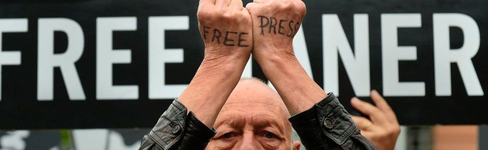 """A man with the words """"free press"""" written on the backs of his hands protests at EU headquarters in Brussels on 25 July 2017"""