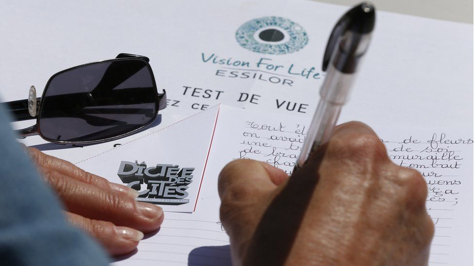 A person takes part in the 'Dictee des cites' an open-air free dictation exercise for adults and children in Saint-Denis, near Paris (May 2015)