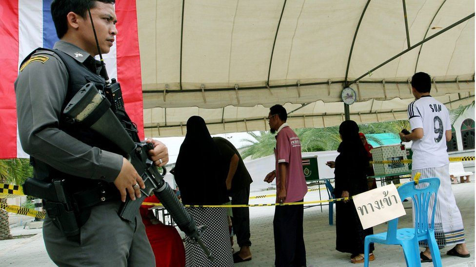 A Thai policeman stands guard during a vote on a new constitution