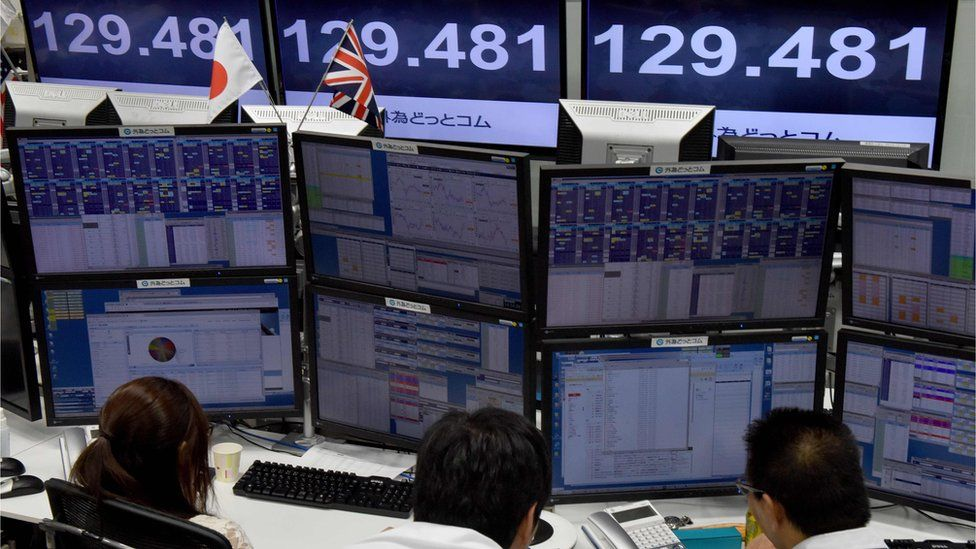 Traders check computer screens showing the Japanese yen rate against the British pound at a brokerage in Tokyo on October 7, 2016