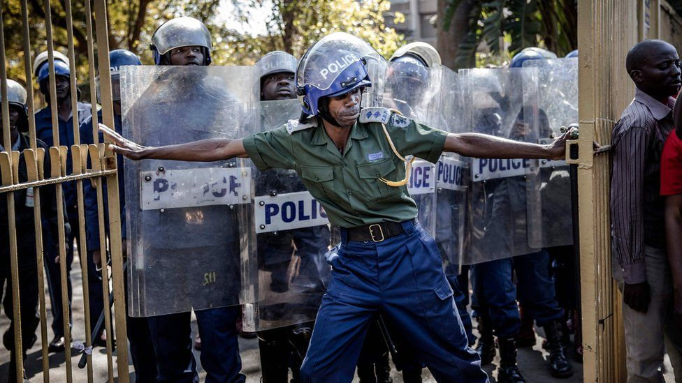 Zimbabwean anti riot police officers close the gate of the Rainbow Towers where the election's results were announced, as supporters of the opposition party Movement for Democratic Change (MDC) protest against alleged widespread fraud in Harare, 1 August 2018