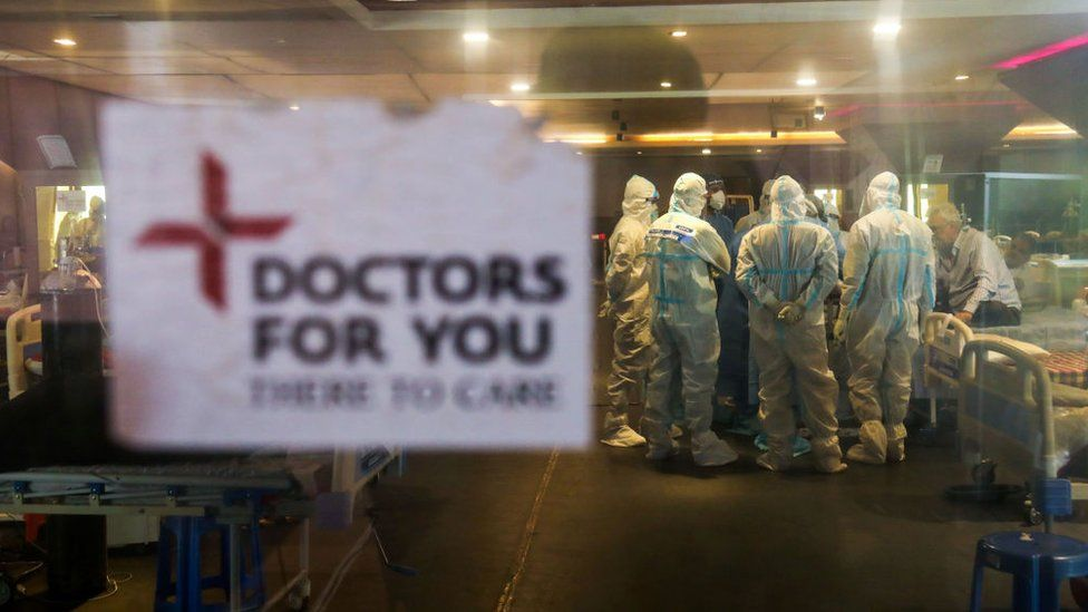 Doctors and healthcare staff wearing Personal Protective Equipment suits (PPE) attend to Covid-19 patient inside a Covid-19 care center in Delhi.