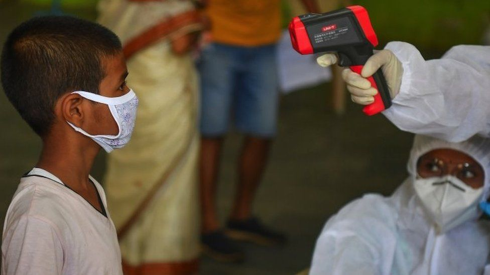 Medical staff take the temperature of a child at a COVID-19 coronavirus community clinic