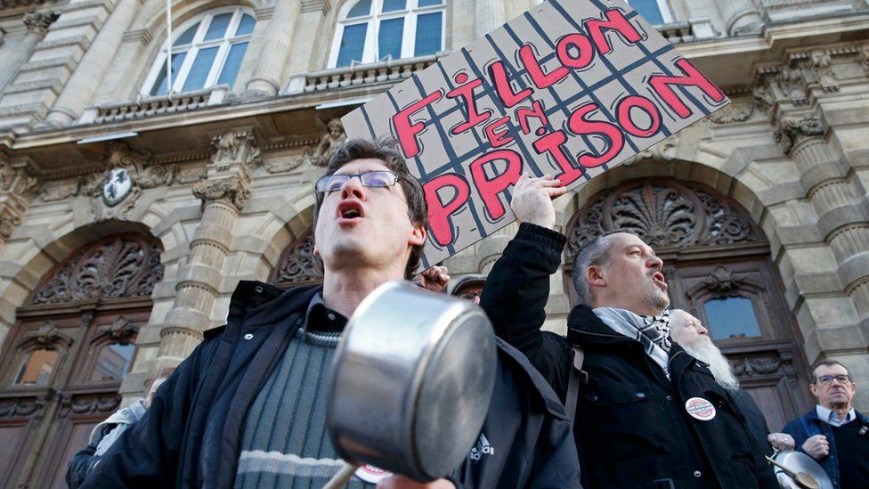 """Demonstrators protest with pots and a placard that reads """"Fillon in prison"""" - 17 February 2017"""