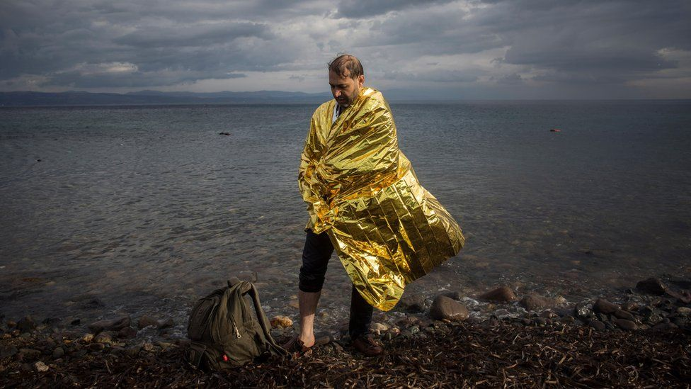 A man wearing a thermal blanket provided by volunteers stands on the shore of a beach after his arrival with other refugees and migrants from the Turkish coast to the northeastern Greek island of Lesbos, on Wednesday, 25 November 2015.
