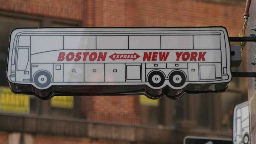 A sign advertising bus services between Boston and New York
