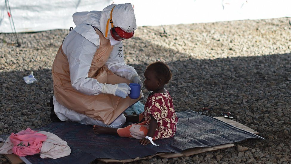A child being fed by a medical worker in a protective suit