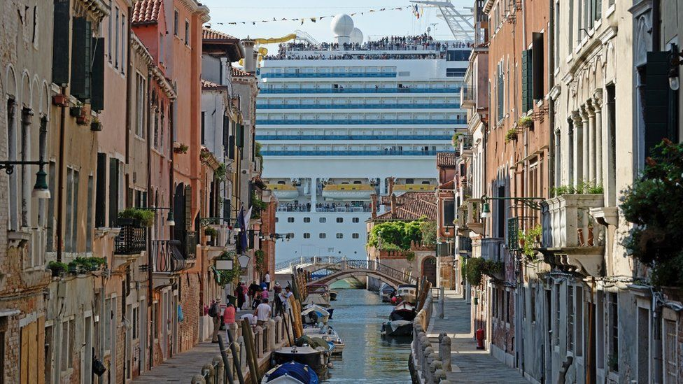 A large cruise ship visible at the end of a narrow canal in Venice
