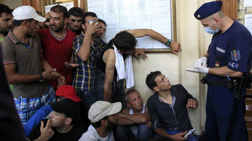 Police speaking to migrants at a Budapest train station, 31 Aug 15
