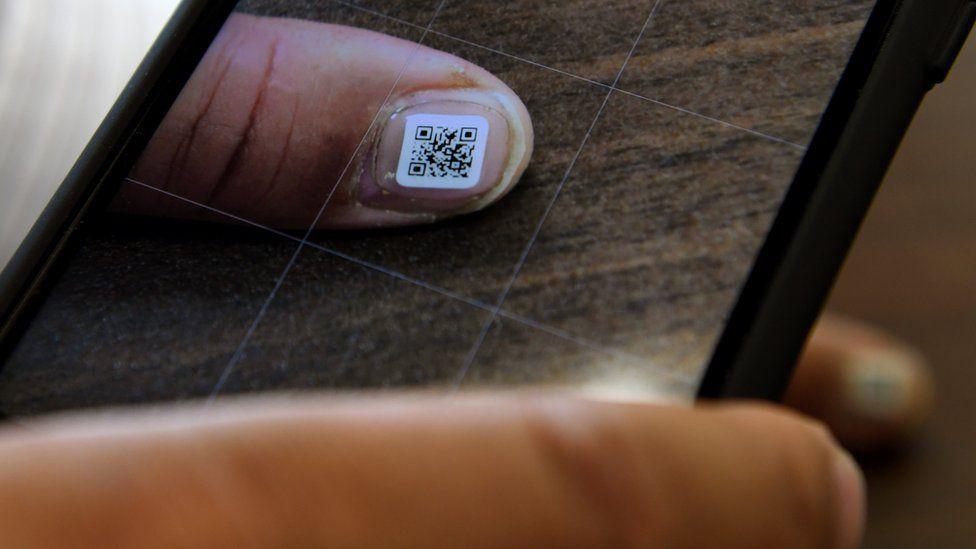An Iruma city official scans the QR code displayed on a fingernail using a smartphone, 5 December 2016