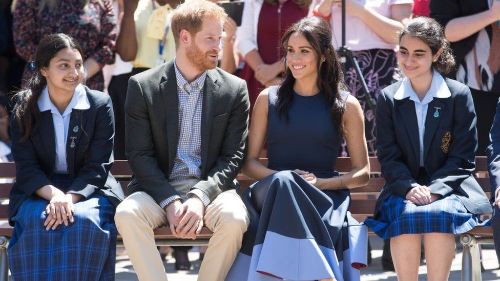 Meghan Markle and Prince Harry sit with some school girls